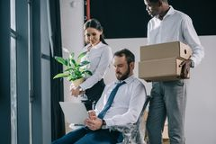 Multiethnic business people with laptop boxes and potted plant moving. In new office royalty free stock photos