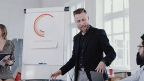 Multiethnic business people listen to middle aged coach man explaining sales at modern office, slow motion RED EPIC. Successful marketing mentor expert stock video