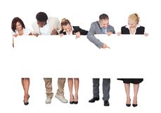 Multiethnic business people looking at blank billboard. Full length of multiethnic business people looking at blank billboard over white background royalty free stock photography