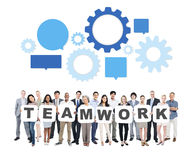 Multiethnic Business People with Teamwork Concept. Group of Multi-Ethnic Business People Holding Letters To Form Teamwork And Speech Bubbles With Gears Above royalty free stock photo