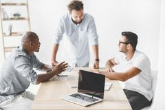 multiethnic businessmen discussing new business idea at workplace stock photography