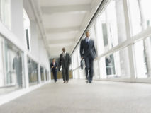 Multiethnic Businessmen Walking In Office Corridor Stock Photo