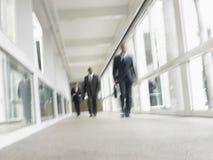 Multiethnic Businessmen Walking In Office Corridor Stock Photo
