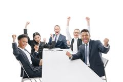 Multiethnic businesspeople in formal wear celebrating success. Isolated on white stock photos