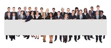 Multiethnic businesspeople holding blank billboard Royalty Free Stock Photography