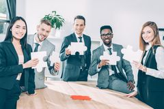 Multiethnic businesspeople holding puzzle pieces together. In conference hall royalty free stock photography