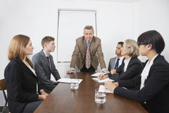 Multiethnic businesspeople at meeting in conference room stock images