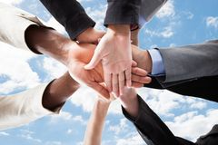 Multiethnic businesspeople's hands on top of each other Stock Photos