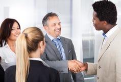 Multiethnic businesspeople shaking hand Stock Photos