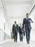Multiethnic Businesspeople Walking In Office Corridor Stock Photos