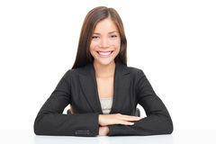 Multiethnic businesswoman sitting at desk smiling Stock Photo