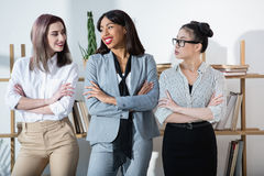 Multiethnic businesswomen in formal wear standing with arms crossed Royalty Free Stock Photography