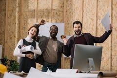 multiethnic celebrative ομάδα των αρχιτεκτόνων με τα έγγραφα στοκ φωτογραφία