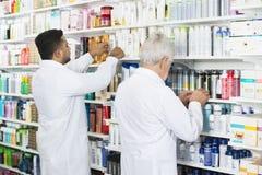 Multiethnic Chemists Arranging Stock On Shelves Stock Photos