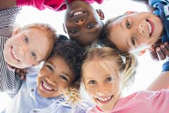 Multiethnic children in a circle. Closeup face of happy multiethnic children embracing each other and smiling at camera. Team of smiling kids embracing together stock photo