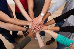 Multiethnic college students stacking hands stock images