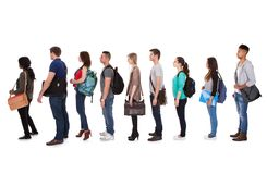 Multiethnic college students standing in a row. Full length side view of multiethnic college students standing in a row against white background Royalty Free Stock Image