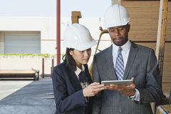 Multiethnic contractors using tablet PC at timber yard Royalty Free Stock Photos