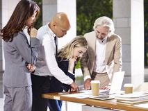 Corporate executives meeting discussing business in modern build. Multiethnic corporate people meeting discussing business using laptop computer in modern Royalty Free Stock Photo