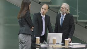 Three corporate executives meeting in modern office. Multiethnic corporate people meeting in office discussing business using laptop computer in modern office stock image