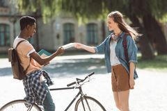 Multiethnic couple with books and bicycle. African american student with bicycle and female student with books near college Royalty Free Stock Photos
