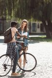 Multiethnic couple with books and bicycle. African american student with bicycle and female student with books near college Royalty Free Stock Photo