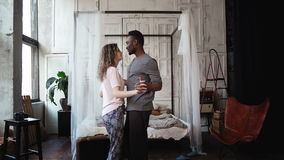 Multiethnic couple dancing in pajamas. African male and Caucasian female look happy, laughing and smiling, holding hands. Young multiethnic couple dancing in royalty free stock images