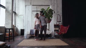 Multiethnic couple gather in travel. Woman holds suitcase, man holds plant. Boy and girl kisses and goes away. Young multiethnic couple in pajamas gather in a stock video footage