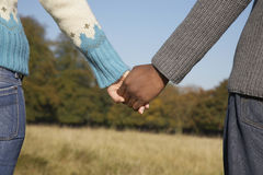 Multiethnic Couple Holding Hands In Field Royalty Free Stock Image