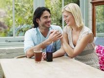 Multiethnic Couple Holding Hands At Verandah Table Stock Photos