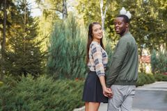 Multiethnic couple in love walk in park back view. Multiethnic couple in love. Young african-american men and asian women walk in park, holding hands, back view Royalty Free Stock Image