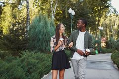 Multiethnic couple in love walk in park. Multiethnic couple in love. Young african-american men and asian women walk in park and having coffee, copy space Royalty Free Stock Photography