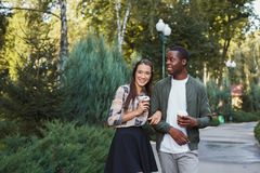 Multiethnic couple in love walk in park. Multiethnic couple in love. Young african-american men and asian women walk in park and having coffee, copy space Stock Images