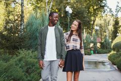 Multiethnic couple in love walk in park. Multiethnic couple in love. Young african-american men and asian women walk in park, holding hands, copy space Stock Image