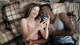 Multiethnic couple lying on bed and using smartphone. Man and woman happy together. Male and female laughing, smiling. Stock Photos