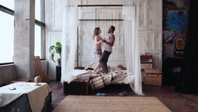 Multiethnic couple in pajamas having fun together. African man and european woman dancing, jumping on bed, laughing.
