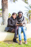 Multiethnic couple in a park. Latina girl and black men listening music sitting Royalty Free Stock Image