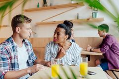 Multiethnic couple quarreling. Upset young multiethnic couple quarreling and looking at each other in cafe Royalty Free Stock Photo