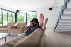 Multiethnic couple relaxing at  home with tablet computers Stock Image