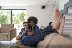 Multiethnic couple relaxing at  home with tablet computers Royalty Free Stock Photography