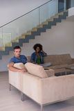 Multiethnic couple relaxing at  home with tablet computers Royalty Free Stock Photo