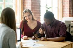 Multiethnic couple signing house purchase agreement. Stock Photo