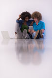 Multiethnic couple sitting on the floor with a laptop and tablet Royalty Free Stock Photos