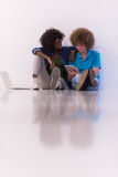 Multiethnic couple sitting on the floor with a laptop and tablet Stock Photography