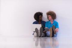 Multiethnic couple sitting on the floor with a laptop and tablet Royalty Free Stock Photography
