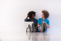 Multiethnic couple sitting on the floor with a laptop and tablet Stock Images