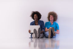 Multiethnic couple sitting on the floor with a laptop and tablet Stock Photo