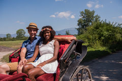 Multiethnic couple sitting in a horse carriage Stock Photos
