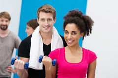 Multiethnic couple working out with dumbbells Stock Photos
