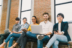 Multiethnic diverse group of young and adult people using smartphone, notebook computer, digital tablet together royalty free stock photography